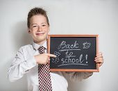 Smiling schoolboy with empty black chalkboard