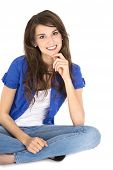 Isolated Young Pretty Smiling Teenager Sitting In Crossed Legs On The Ground.