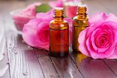 foto of massage oil  - Essential aroma oil with roses on wooden background - JPG