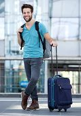 Young Man Waiting At Airport With Suitcase And Bag