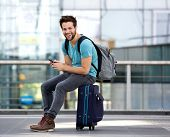 Man Sitting On Suitcase And Sending Text Message
