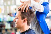 Female coiffeur cutting men hair in hairdresser shop