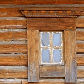 A small window in the wall of an old wooden house