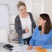 Female Boss Praise Her Young Assistant In The Office.