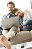 Couple Relaxing On Sofa With Laptop