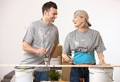 Happy casual caucasian couple at new home having fun painting. Smiling, looking at each other, stand
