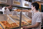 stock photo of pizza parlor  - Young guy buys a slice of pizza in a modern restaurant - JPG