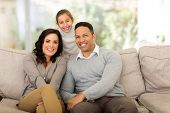 happy family of three relaxing together at home