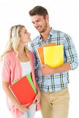 Attractive student couple smiling at each other on white background