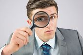 Businessman looking through magnifying glass on grey background
