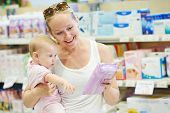 woman choosing hygienic tissues or napkin with little baby child on hands in shop supermarket