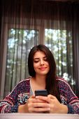 Happy woman sitting at the table and using smartphone at home