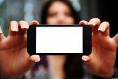 Closeup portrait of a woman showing smartphone screen