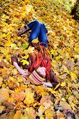 Smiling woman resting on autumn leaves in park.
