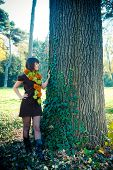 Young woman hiking in autumn park dressed in knitted dress and scarf.