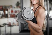 Woman Workout With Dumbbell In Gym