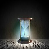 image of hourglass figure  - Conceptual image with sandglass and silhouettes of business people around - JPG