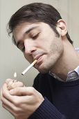 picture of cigarette lighter  - Youbg Man with tobacco cigarette using lighter - JPG
