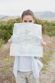 Portrait of a hiking young woman holding map on mountain terrain