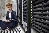 Happy technician sitting on floor beside server tower using tablet pc in large data center