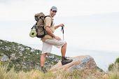 Full length portrait of a hiking man walking on mountain terrain