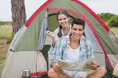 Portrait of a smiling young couple with map sitting outside their tent