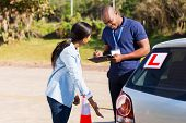 female african student driver doing pre test inspection in testing ground