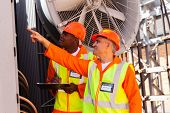 senior technician and young electrician working together in power plant