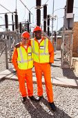 portrait of two electricity workers standing in substation