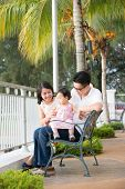 Happy Asian family portrait sitting at outdoor bench.