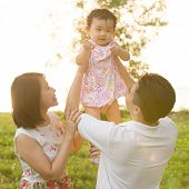 Portrait of happy Asian family playing together at outdoor park during summer sunset.