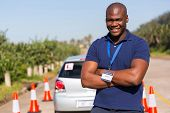 handsome afro american driving instructor with arms crossed