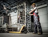 stock photo of heavy equipment operator  - Young worker moving paving stones with pallet truck on a factory - JPG