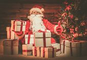 Santa Claus sitting on a carpet  in wooden home interior with gift boxes around him