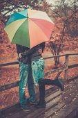 Middle-aged couple with umbrella outdoors on beautiful rainy autumn day