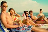 stock photo of sunbather  - Group of multi ethnic friends sunbathing on a deck chairs on a beach  - JPG