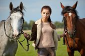 Young beautiful woman and two horses outdoors