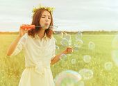 Young Woman Blowing Soap Bubbles In Summer