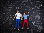stock photo of frot  - Cute boy and girl learning playfully in frot of a big blackboard - JPG