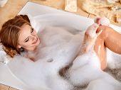 Young woman wash leg in bathtube.
