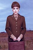 Fine art portrait of a gorgeous young blond female army officer in a stylish uniform holding a small vintage case standing in the field at the front, conceptual image