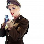 Glamorous young blond female army officer aiming a rifle at the camera with focus to her face and parted red lips, over white with copyspace