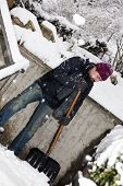 stock photo of snow shovel  - a man is snow shoveling the stairs - JPG