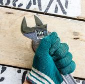 Hand Holds Wrench And Tighten The Nut On The Wooden Floor.