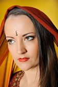 Young Beautiful Woman In Indian Traditional Jewellary, Bindi And Sari Dress. Yellow Background