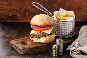 picture of wooden basket  - Burger with meat and French fries in basket on wooden background - JPG