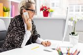 foto of self-employment  - Woman talking on phone while working with computer in the office - JPG