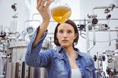 Stylish girl in denim jacket holding beaker of beer in the factory