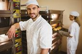 Handsome baker smiling at camera in a commercial kitchen