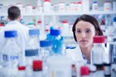 Portrait of a chemist behind medical sample in lab